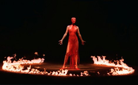 LONDON - FEBRUARY 25: A model wearing a red hooded cat suit, stands among a ring of fire on February 25, 1998 during the finale of British designer Alexander McQueen's autumn/winter 1998/99 fashion collection on the last day of London Fashion week. (Photo by Paul Vicente/AFP/Getty Images)