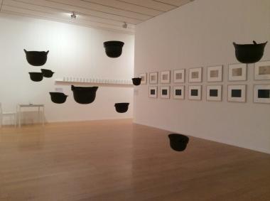 """Vue de l'exposition Yoko Ono: """"Helmets"""". Casques de la seconde guerre mondiale suspendus...."""